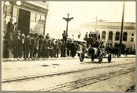 Early model racecar with driver and passenger travels along street past sidewalk full of spectators, Bellingham, WA (Mt. Baker Marathon)