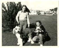 A woman crouches with a small dog in her arms next to a woman standing with a large dog on a leach
