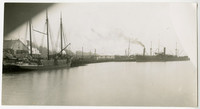 View from water of three-masted cargo ship at lumber mill dock with several steam cargo vessels in background