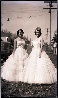 Women in formal dresses, possibly as part of beauty pageant, stand in row