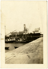 View from dock of large steamer, S.S. North King docked at Alitkak harbor on Kodiak Island, AK, with smaller fishing vessels in foreground