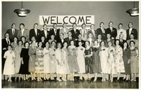 Large group of men and women in party attire pose in three rows in front of welcome banner