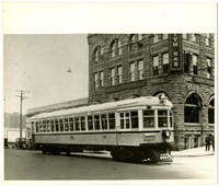 Electric Interurban trolley car #75 at the corner of State and Holly streets, Bellingham, WA, with the four-story stone Puget Sound Power & Light building in background
