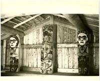 Three coast-Salish totem lodge poles inside a lodge