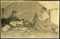 Two women and a man sit inside a tent