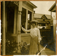Woman wearing captain's hat stands with hand leaning against pillar of front porch with other houses and clothesline in background