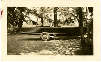 Small speedboat mounted on trailer parked among trees