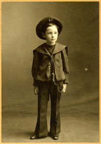 Young boy in wide-brinned hat and sailor's suit in studio portrait