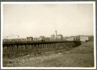 Streetcar trestle spans barren field with buildings of Spokane in distance, and Spokane County Courthouse in center