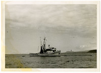 View from water of purse seiner with net floating on water, near Aleutian Islands, AK