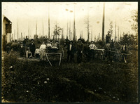 Five men, one woman, five children pose with horses, a buggy, and a wagon, with a partially cleared forest in background