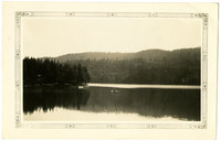 Placid lake with forested shoreline reflecting on surface