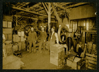 Roy Weaver, (father of Roy Frank Weaver), Henry Lind, and Charles Christianson stand among boxes and machinery in canning factory at the American Can Company