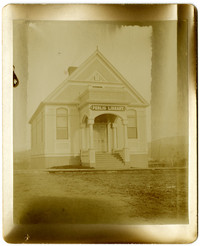 """A very faded photogrpah of a small, single-story building with pillared portico and sign reading """"Public Library"""""""