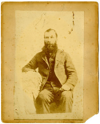 Studio portrait of seated unidentified bearded man in suit
