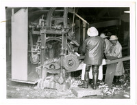 Three men in rain gear working the butchering machine which gutted and cleaned salmon, as evident by drippings and fish parts on floor