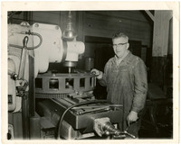 Man in overalls stands next to piece of industrial equipment, possibly in a cannery
