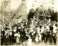 Large crowd of men, women, and children at White City amusement park at Lake Whatcom with roller coaster and ferris wheel