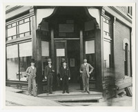 Four men in suits and hats stand outside doors of Riedel & Moffat - Real Estate at the corner of Harris avenue and 11th street, Fairhaven (later Bellingham), WA