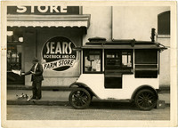 Mobile popcorn vendor parked in front of Sears and Roebuck Farm Store while man feeds popcorn to pigeons