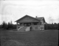 Large, three-story house or club-house with large front stairs and porch sitting alone on large grounds.