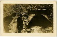 Two men inspect water passing through culvert