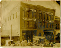 Exterior of Washington Wholesale Grocery Co. with horse-drawn wagon and goods in front of building