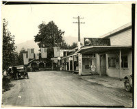 Gateway Grocery store and automobile service station in Glacier, WA, with several early model cars and American flags strung above road