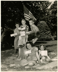 Five children holding ration books pose atop cannon monument in Elizabeth Park, Bellingham, WA