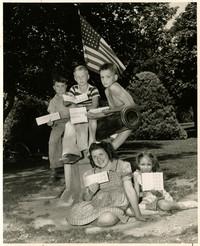Five children holding ration books pose atop cannon monument in Elizabeth Park, Bellingham, WA