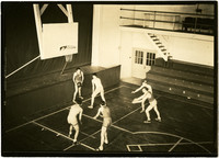 Six men play basketball in Whatcom High School gymnasium