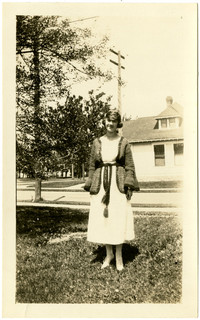 Young woman in dress and sweater poses on front lawn