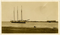 View from shore of three-masted vessel at Nelson Lagoon, Alaska, with warehouse on land opposite