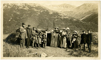 Group of caucasion men, women, and children pose at entrance to Inuit cave dwelling