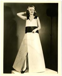 Woman poses on modeling platform in full-length dress