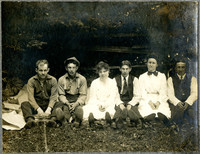 group of four young men and two young women seated in a row under a tree