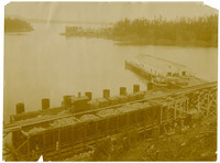 Lime kiln operation at Roche Harbor, WA, seen from above with trestled railroad tracks and train with cars full of lime stones above the hoppers full of limestone, ready for the kilns directly below