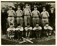 Ten members of the Fairhaven high school baseball team pose in uniform in two rows, with coaches at back