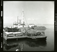 Two men standing on a pier, looking toward a heavily laden barge labelled Juneau