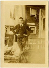 Teenage boy wearing jhodpurs and high boots poses leaning against a pillar