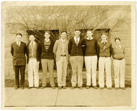 Fairhaven High - Seven teenage boys in sweaters and jackets, and one teacher pose on sidewalk