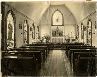 Interior of small chapel showing altar, stained glass windows, and pews