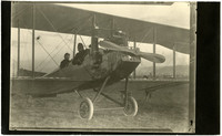Two people sit in open cockpit of single propeller biplane parked on grass