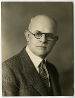 Studio portrait of Dr. Orville Beebe in spectacles and tweed jacket
