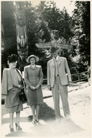 Two women and a man pose in front of Native American totem poles