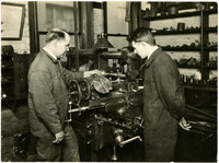 Two mechanics in machine shop using a metal lathe