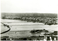 View of Bellingham Bay from Sehome Hill looking northwesterly over railroad tracks, pilings, and docks of industrial waterfront