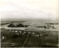 View from distance of warehouses and dock on waterfront with parking lot in foreground