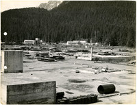 Industrial or cannery site that appears mostly disassembled with several nearly vacant cement platforms in foreground, forested mountains in background