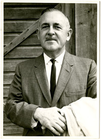 Unidentified man in suit poses in front of wooden structure